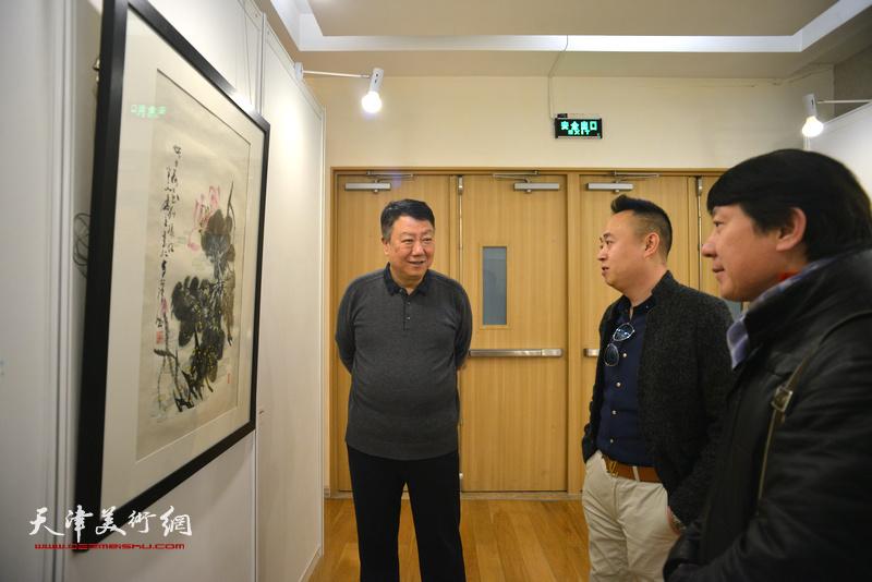郭洪友、主云龙、张明在观赏展出的作品。