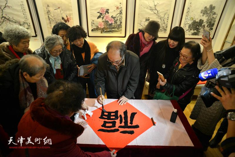 """郭书仁在艺术沙龙展现场写""""福""""迎春。"""