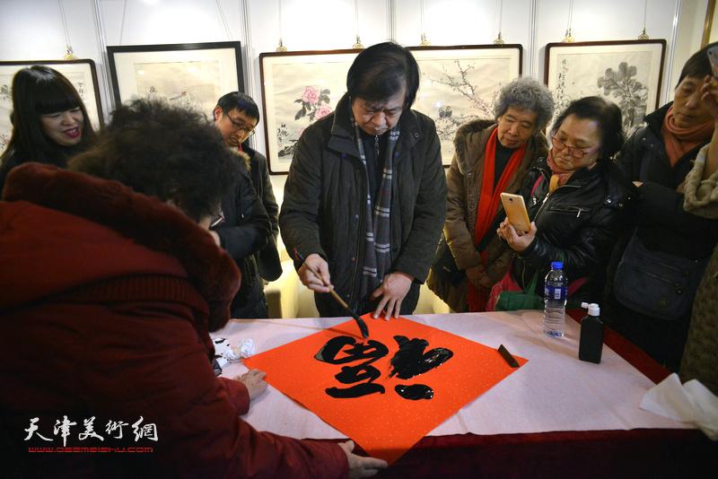 """史振岭在艺术沙龙展现场写""""福""""迎春。"""