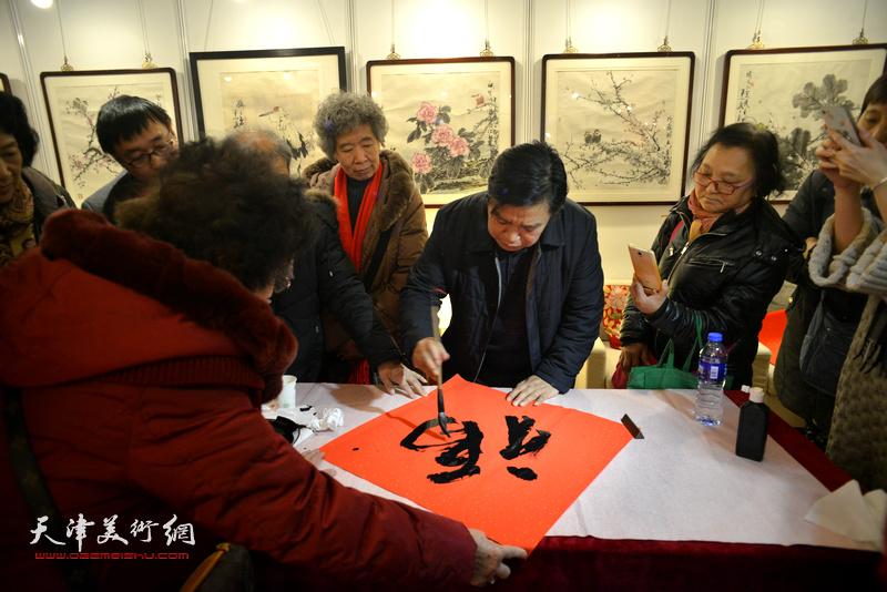 """李耀春在艺术沙龙展现场写""""福""""迎春。"""