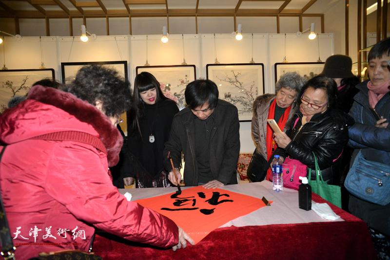 """肖培金在艺术沙龙展现场写""""福""""迎春。"""