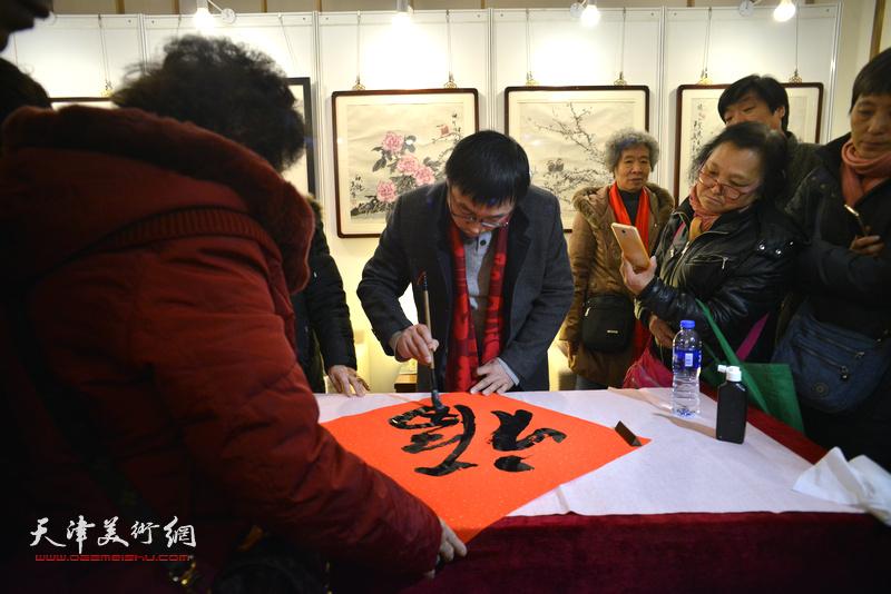 """张枕石在艺术沙龙展现场写""""福""""迎春。"""