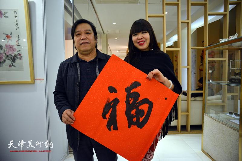 """李耀春、肖冰在艺术沙龙展现场送""""福""""。"""