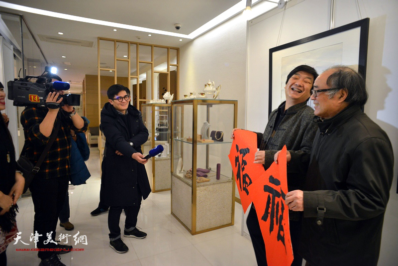 """郭书仁、翟洪涛在艺术沙龙展现场通过电视镜头向观众送""""福""""。"""