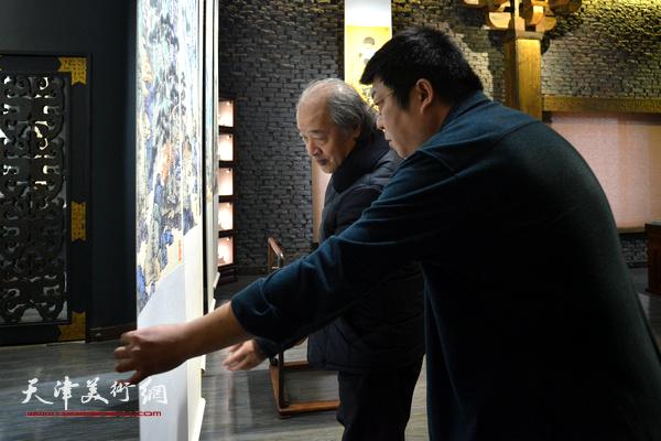 王书平、李博隽在观赏作品馆内展出的李博隽画作。