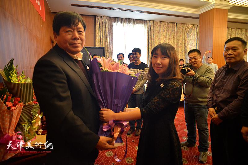 著名画家郭鸿春先生收徒仪式现场,新弟子陈子君向师父献花。