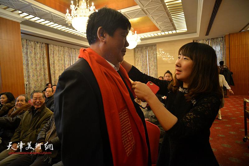 新弟子陈子君为师父郭鸿春带上象征喜庆的红围巾。