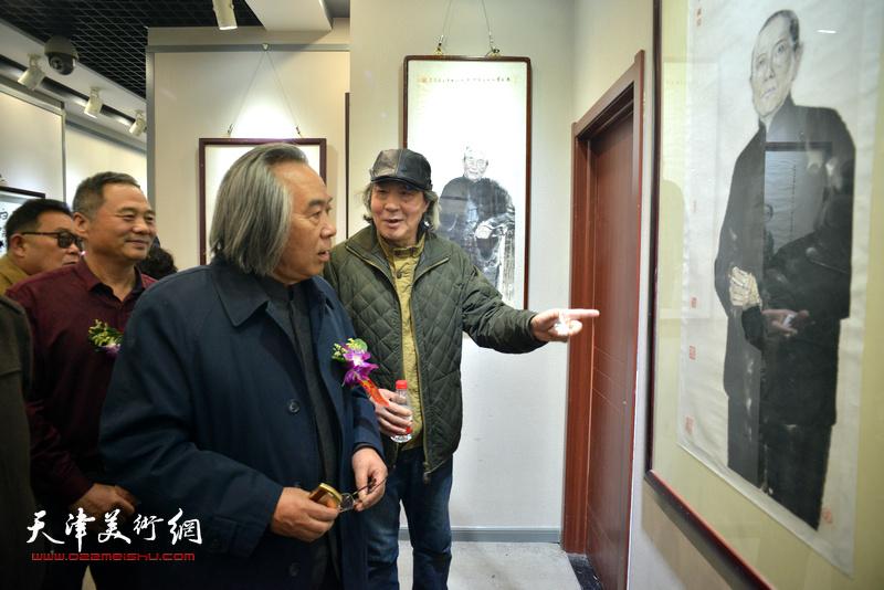 霍春阳、张亚光、邢立宏在观赏展出的作品。