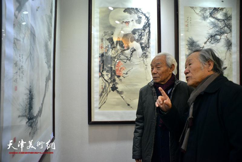 纪振民、姬俊尧在观赏展出的作品。