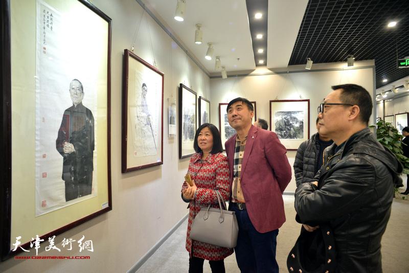 赵长生在观赏展出的作品。