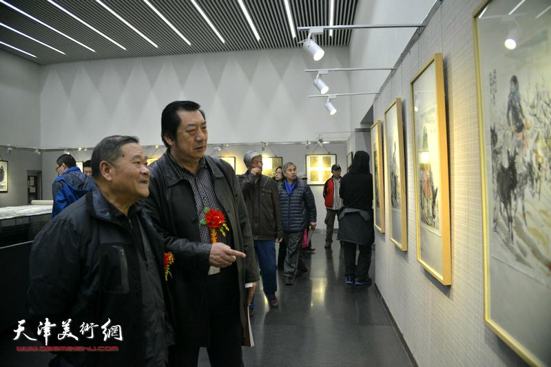 姬俊尧、孙玉河在观赏展出的画作。