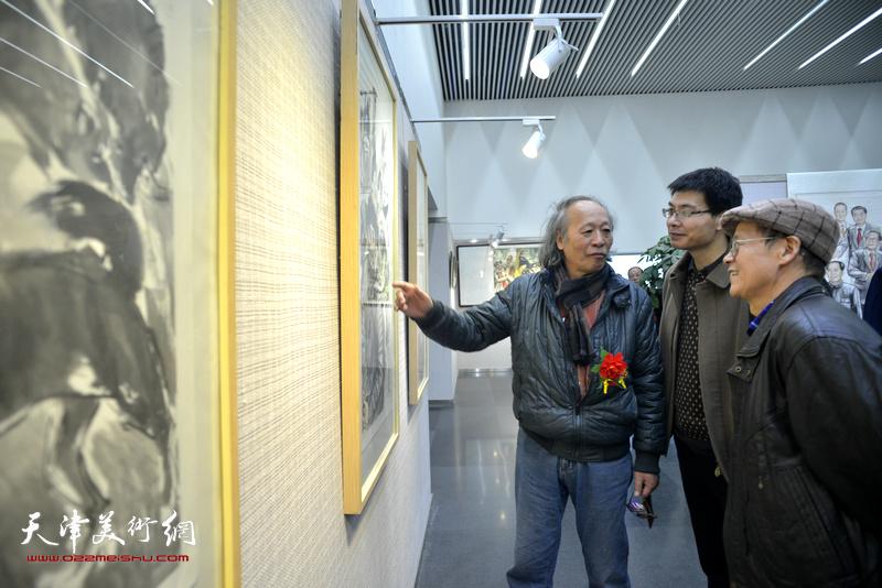 尚金生、王作飞、柳河在观赏展出的画作。