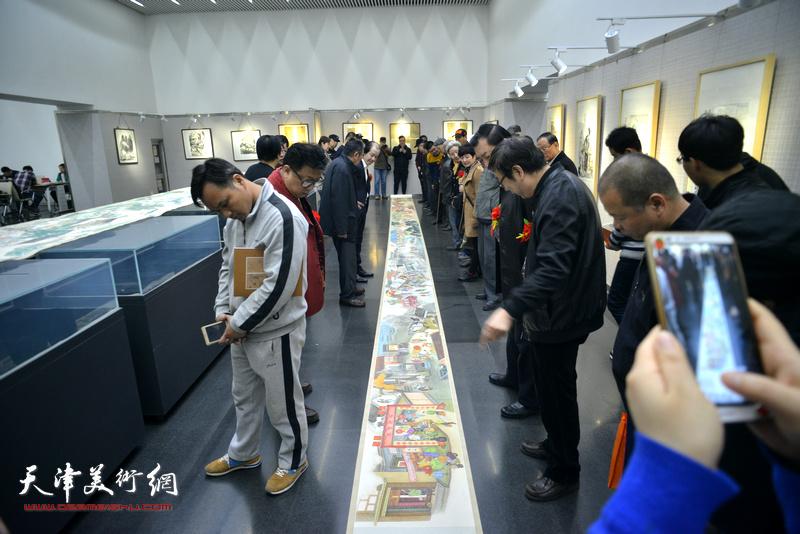 来宾在画展现场观赏刘维仑的《盛世集贸图》和《盛世闹春图》长卷。