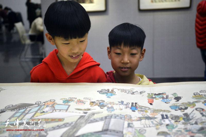 小观众在观赏刘维仑的《盛世集贸图》和《盛世闹春图》长卷。