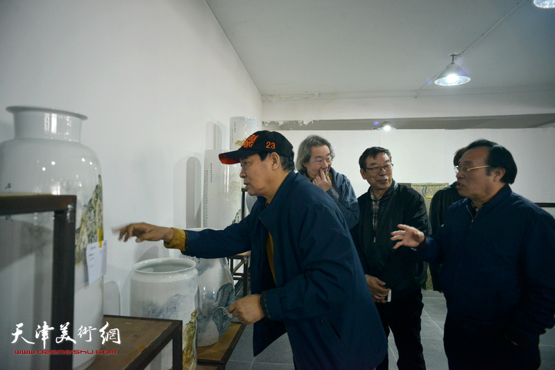 """陈钢向马寒松、张亚光、时景林介绍""""长城青花瓷""""系列作品创作。"""
