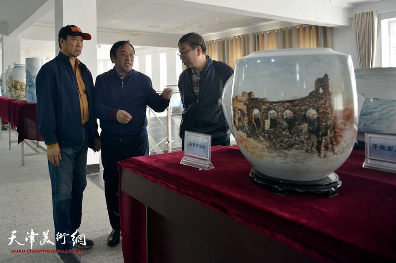 """陈钢向马寒松、时景林介绍""""长城青花瓷""""系列作品创作。"""
