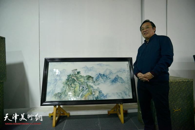 陈钢在创作的《黄崖关长城》瓷板画作品前。