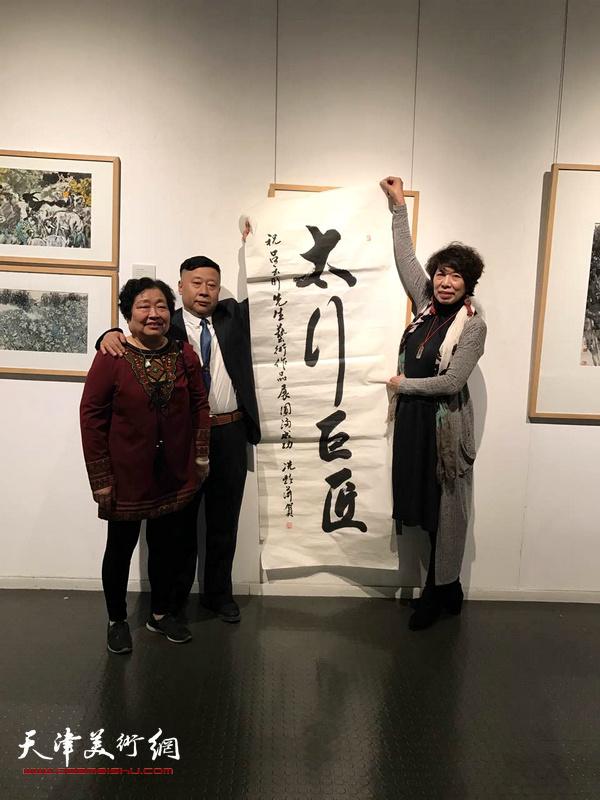 吕大江、张秀茹、吕爱茹在画展现场展示著名女书法家冼艳萍为画展题写的贺词:太行巨匠。