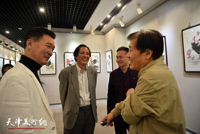 王峰、杨永茂、杨雷鸣在画展现场与陈之海交流。