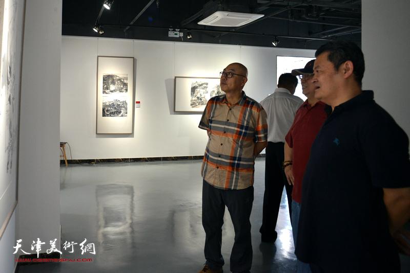 陈嵘、白鹏、高博在观看展出的作品。