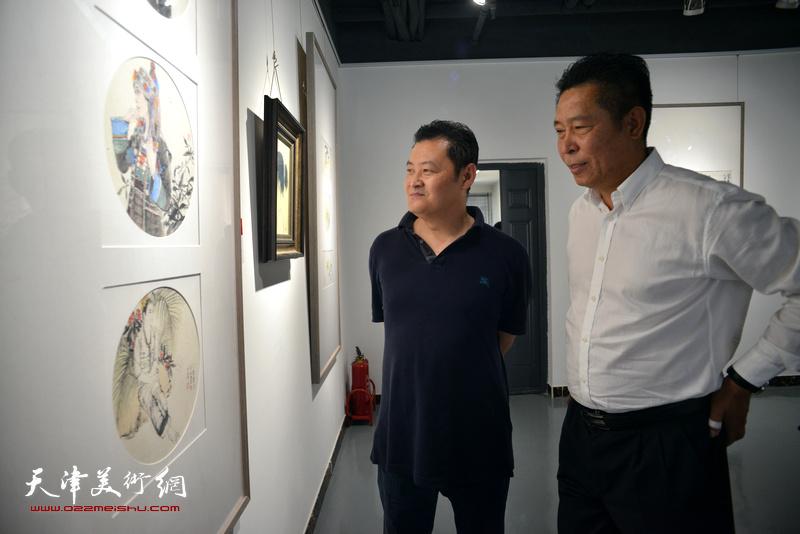 王卫平、李玉忠在观看展出的作品。