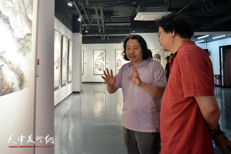 贾广健、晏平在观看展出的作品。
