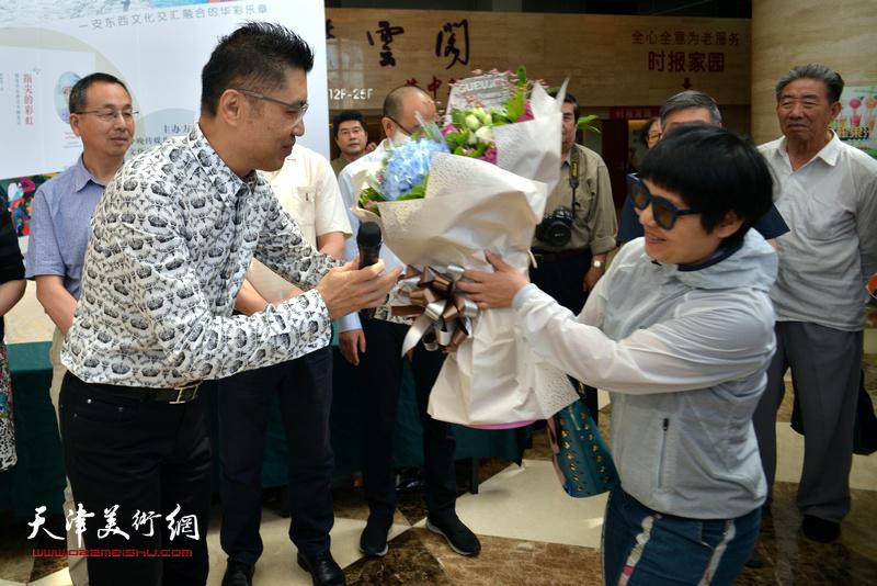 读者向程亚杰献花。