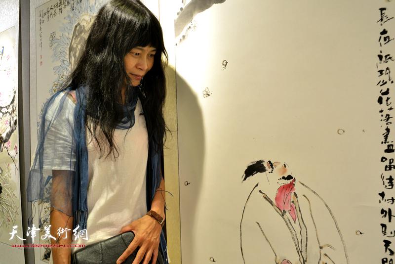 杨晓君与画中人物神会。