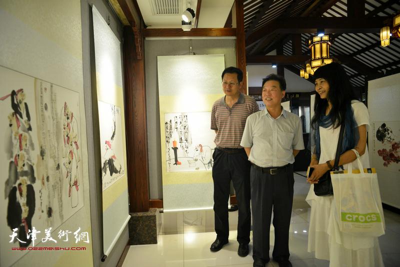 杨建国、潘津生、杨晓君在观看展品。