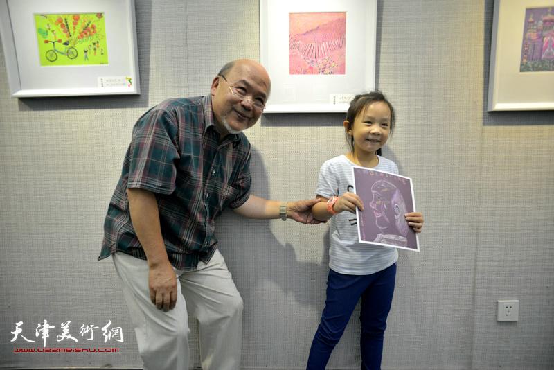 余传生和小作者在画展现场。