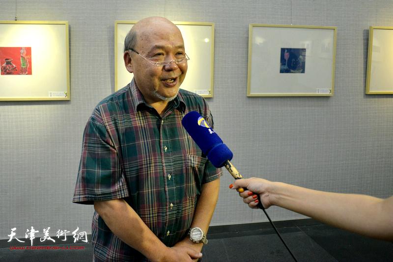 余传生在画展现场接受媒体采访。