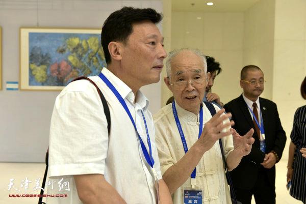 郭文伟向国家海洋局宣教中心领导朱德洲介绍焦墨海洋画创作