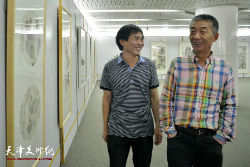 肖培金陪同邓国源观赏展品。