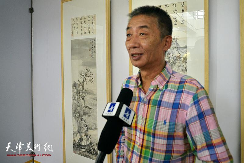 邓国源在画展现场接受媒体采访。