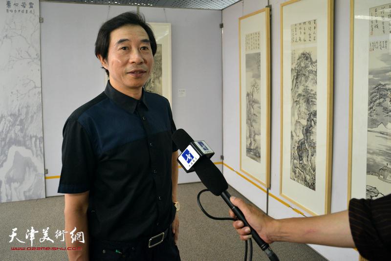 李孝萱在画展现场接受媒体采访。