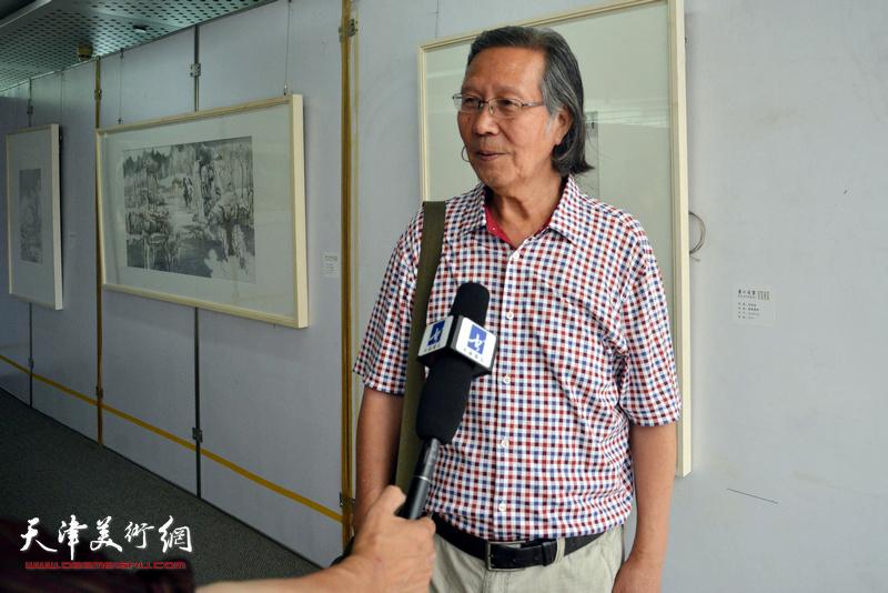 张恩祥在画展现场接受媒体采访。