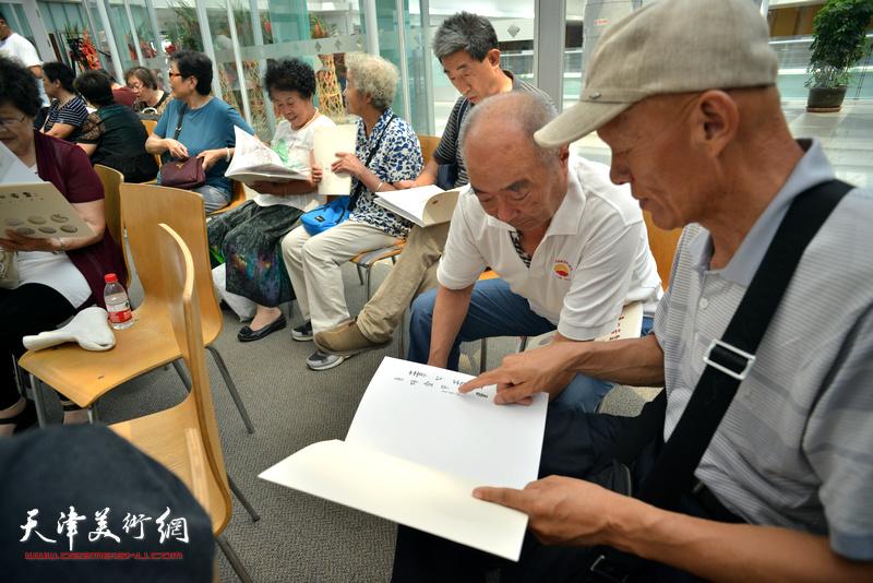 观众在画展现场阅读《素心若雪-肖培金中国画》画集。