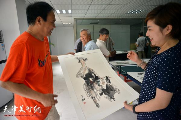 青年画家王霞向马寒松请教笔墨问题。