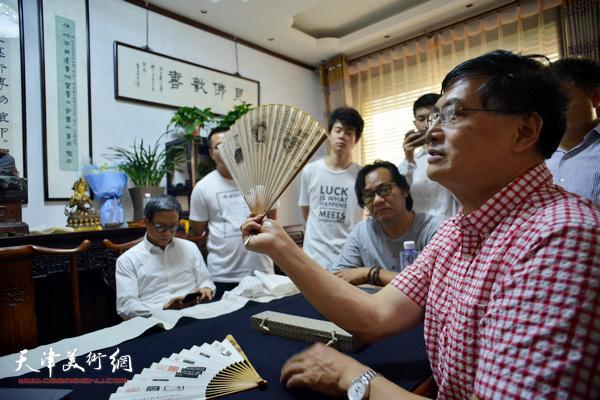 唐存才向津门书画家、爱好者介绍艺术品。