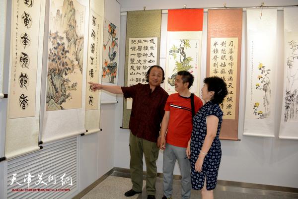 卢勇、杜秀兰、王鸿霖在观赏展出的画作。