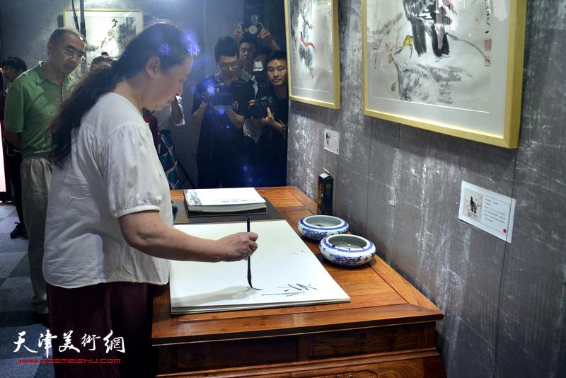 郑岱在光影彩墨艺术馆签到。