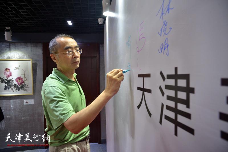 喻建十在光影彩墨艺术馆签到。