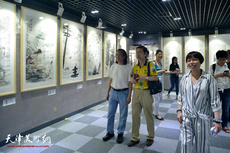 中国电影基金会光影彩墨艺术馆馆长陈德频陪同周世麟、田宝江观看展品。