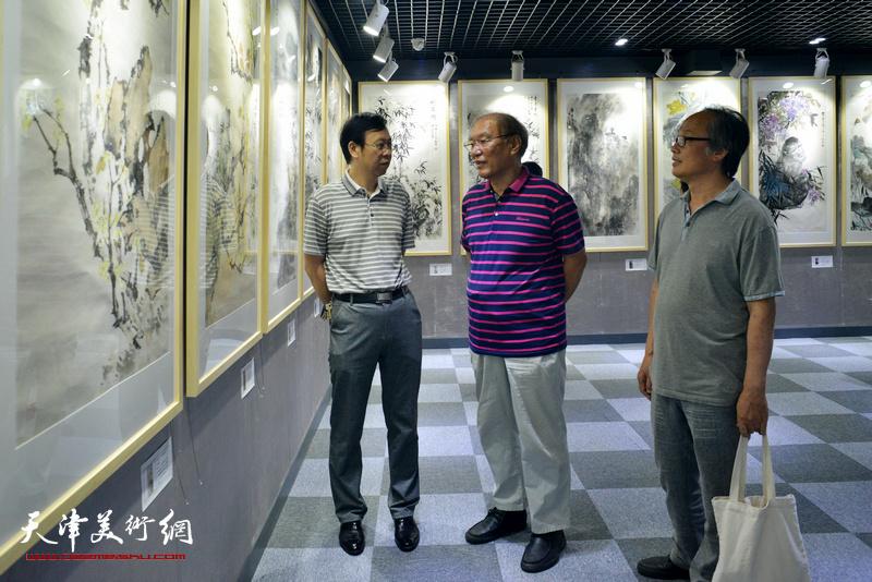 何延喆、陈福春、路洪明在观看展品。