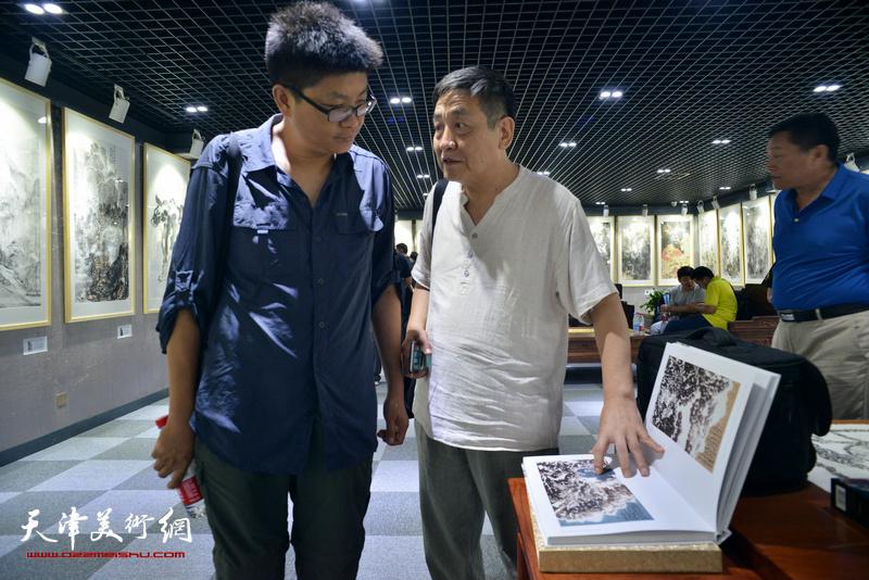 李炳训、李旭飞在画展现场观赏为此次画展出版的画集:《光影彩墨——天津美术学院艺术家中国画精品集》。