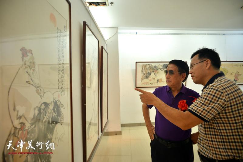 曹中厚、张桂元在观赏展出的画作。