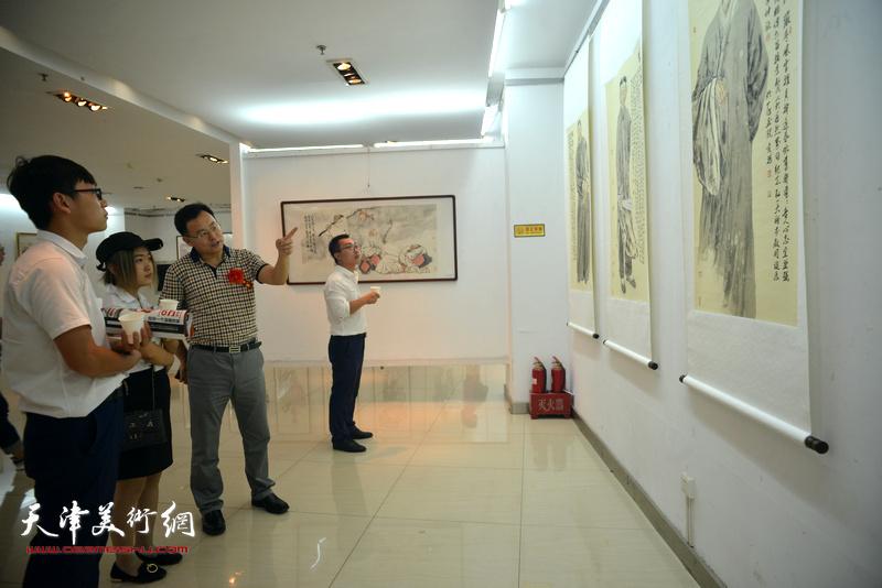 张桂元与美术爱好者在画展现场观赏画作。