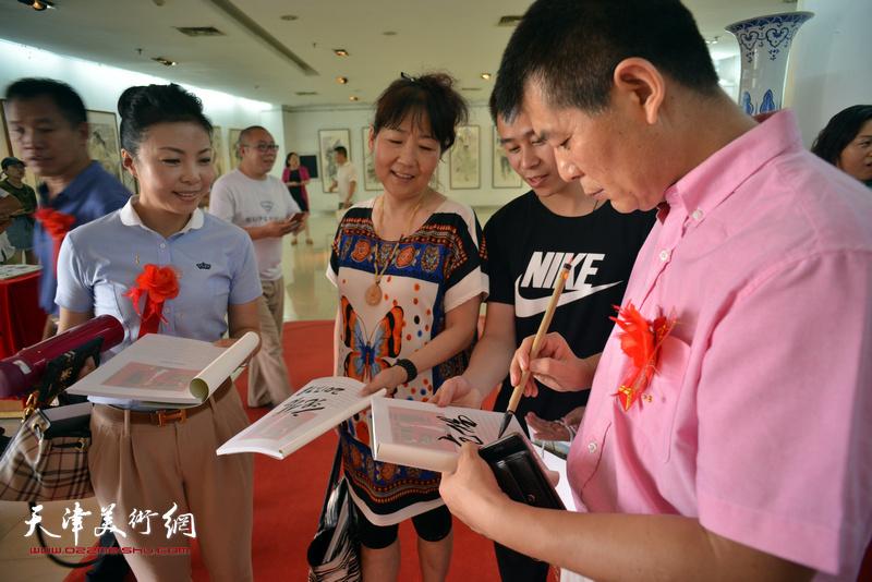 范扬为来宾在画展特刊《心象·墨韵—范扬人物画作品集》签名留念。
