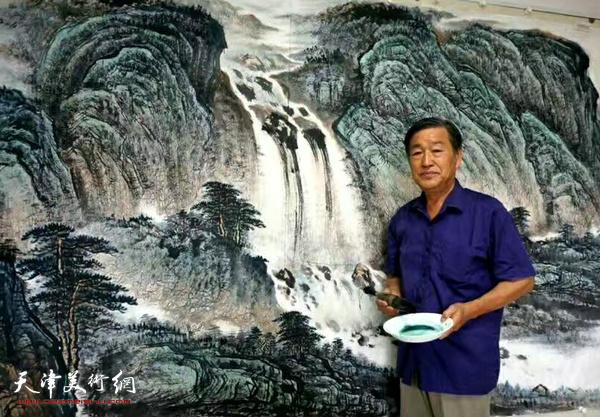 """画家戴照林在山水巨作""""苍山无语水有情""""前。"""
