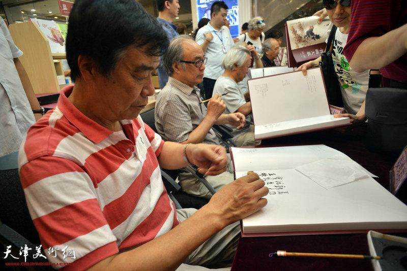 著名文化学者姜维群在《萧朗书画大系》首卷签售仪式上为读者签字。